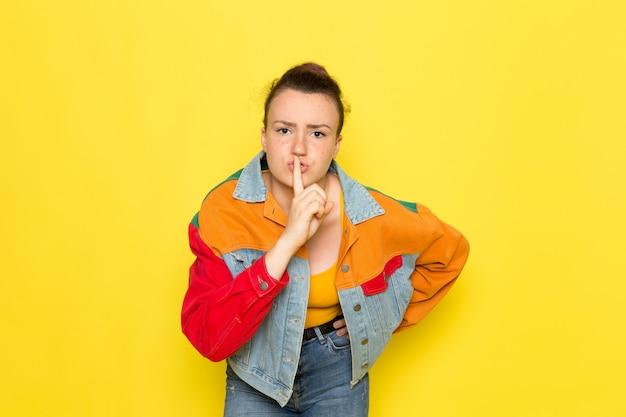 黄色のシャツのカラフルなジャケットと沈黙の兆しを見せブルージーンズの正面の若い女性