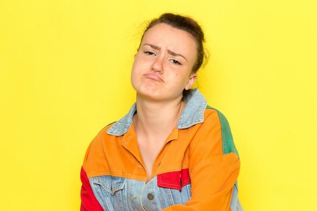 黄色のシャツのカラフルなジャケットと悲しい表情で示すブルージーンズの正面の若い女性