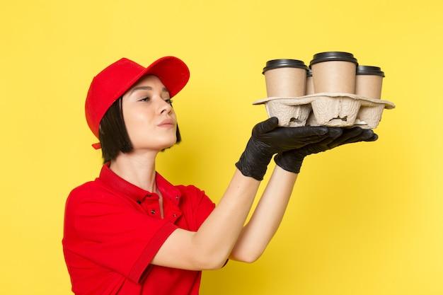 赤い制服の黒い手袋とコーヒーカップを保持している赤い帽子の正面の若い女性の宅配便