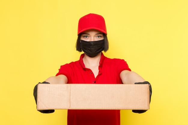 Вид спереди молодой женщины курьер в красной форме черные перчатки и красной кепке держит коробку с едой
