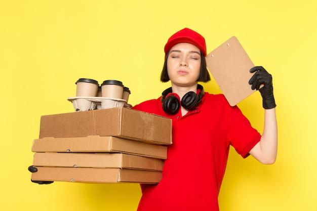 赤い制服の黒い手袋とフードボックスとコーヒーカップを保持している赤い帽子の正面の若い女性の宅配便