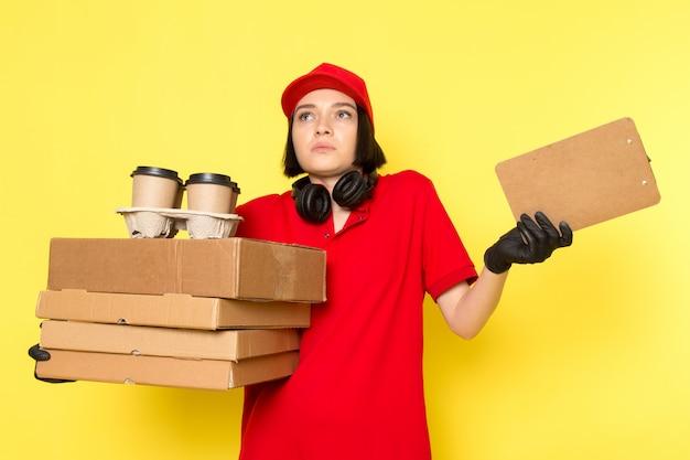 Вид спереди молодой курьер женского пола в красных форменных черных перчатках и красной шапочке с коробками с едой и кофейными чашками