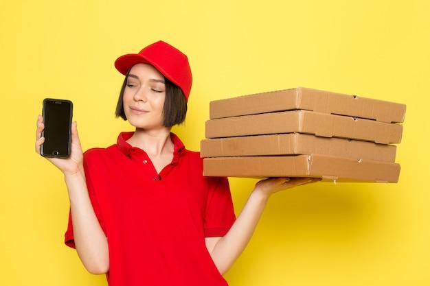 Вид спереди молодой женщины курьер в красной форме черные перчатки и красной кепке, держа коробки с едой и телефон