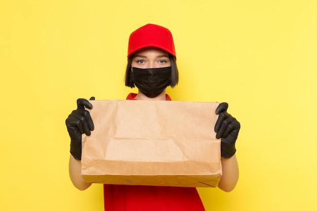 Вид спереди молодой женщины курьер в красной форме черные перчатки и красной шапочке, держа пакет с едой