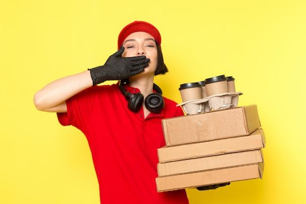 Вид спереди молодой курьер женского пола в красных черных перчатках и красной шапочке с пакетами и коробками с едой
