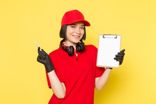 赤い制服の黒い手袋と持株ペンとメモ帳の笑みを浮かべて赤い帽子の正面の若い女性宅配便