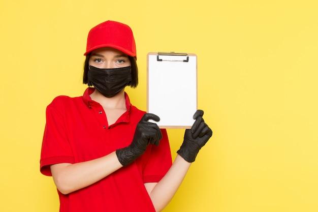 赤い制服の黒い手袋黒いマスクとメモ帳を保持している赤い帽子の正面の若い女性宅配便