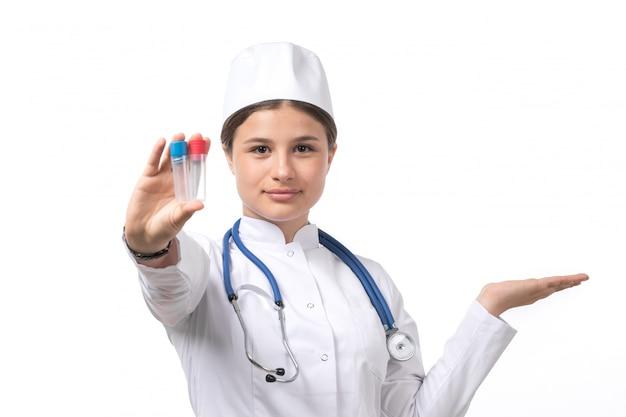 白い医療スーツとフラスコを保持している青い聴診器で白い帽子の正面の若い女性医師