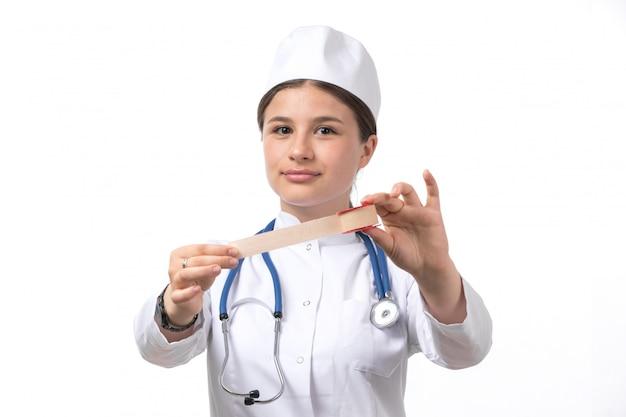 白い医療スーツと医療包帯を保持している青い聴診器で白い帽子の正面の若い女性医師