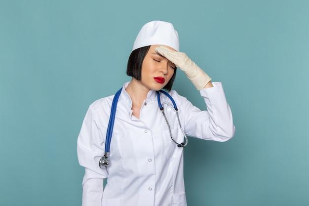 白い医療スーツと頭痛を持つ青い聴診器で正面の若い女性看護師