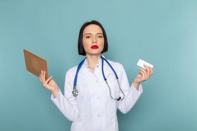 白い医療スーツとメモ帳を保持している青い聴診器で正面の若い女性看護師