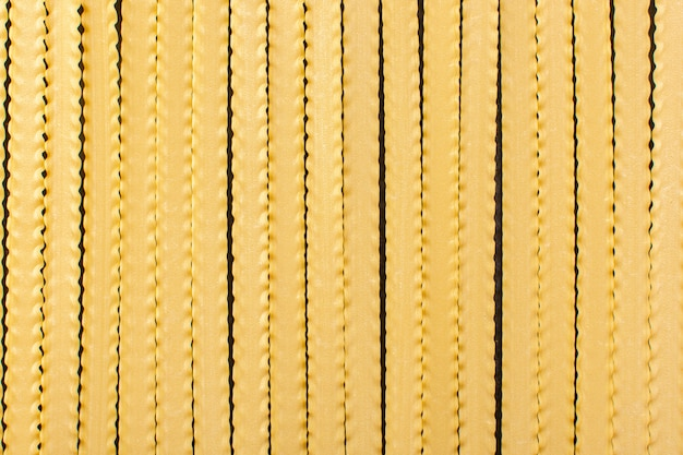 Вид спереди желтые длинные макароны, сформированные сырой итальянской пасты
