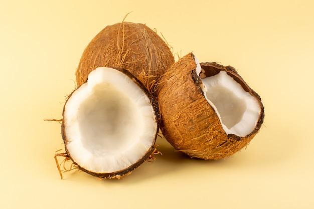 Фронт закрыл вид кокосовых орехов, нарезанных молочно-свежей спелой, изолированных на кремовом фоне тропических экзотических фруктов орех