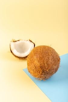 Фронт закрытый вид кокосовые орехи целые и нарезанные молочно-свежей спелой, изолированные на кремово-голубом фоне тропического экзотического фруктового ореха