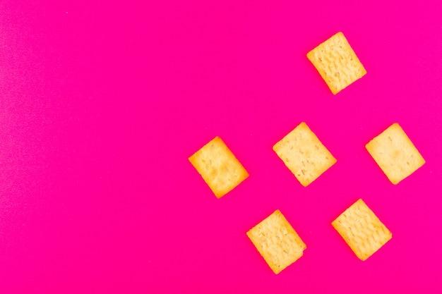 Фронт закрыл вид сухих соленых крекеров крекинга сыра, изолированных на розовом фоне закуски хрустящий крекер