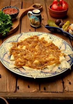 揚げ玉ねぎと肉をトッピングしたヒンガルの葉