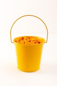 Корзина вид спереди с макаронами сухой итальянской оранжевой пасты внутри желтой корзины на белом