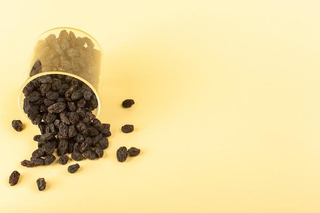 Вид спереди черных сухофруктов внутри пластикового стакана, изолированных на кремовом фоне сухих фруктов черного цвета