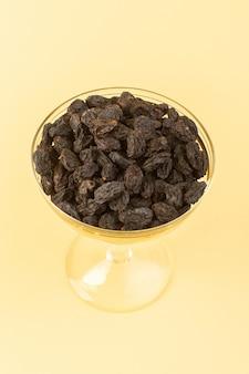 Вид спереди черные сухофрукты кислые сушеные внутри маленького прозрачного стекла, изолированные на кремовом фоне сухих черных фруктов