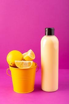 Пластиковая бутылка с шампунем, вид спереди, с черной крышкой и корзиной, полной лимонов, изолированных на фиолетовом