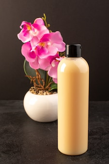 Вид спереди кремового цвета, пластиковая бутылка, шампунь с черной крышкой с цветком, изолированный на темном фоне косметика для волос