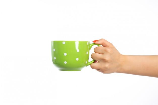 Вид спереди женская рука держит зеленую чашку на белом