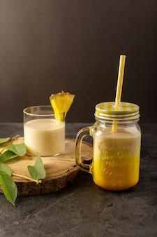 Вид спереди свежий коктейль вкусный прохладительный напиток внутри банки с соломой возле деревянного стола вдоль зеленых листьев на темном фоне пить летний сок