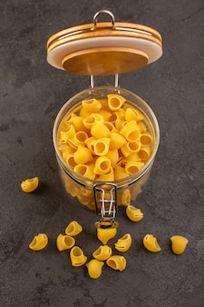 Вид спереди итальянская сухая паста желтого сырья внутри чаши, изолированных на темном