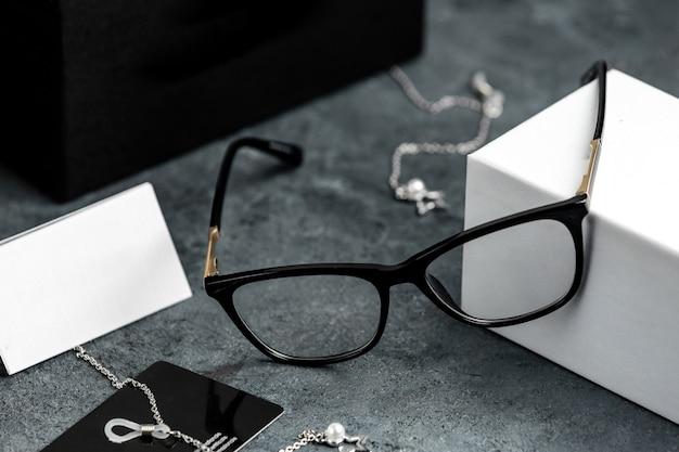 シルバーブレスレットが付いている灰色の机の上の正面の光学サングラス分離された視力の目
