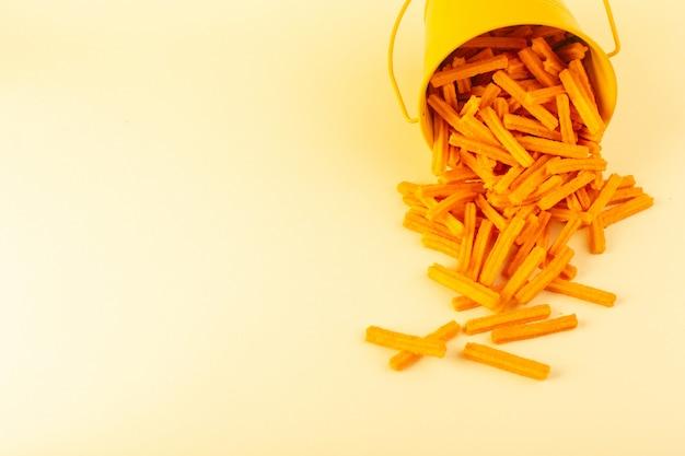 バスケットの中の正面図パスタは、クリーム色の背景の食事食品パスタに黄色のバスケットの中にオレンジの生を形成しました