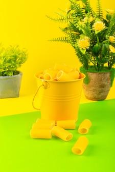 バスケット内の正面のパスタは、黄緑色の背景の食事の食べ物のイタリアンスパゲッティの植物と一緒に、黄色のバスケットの中に生で形成されました