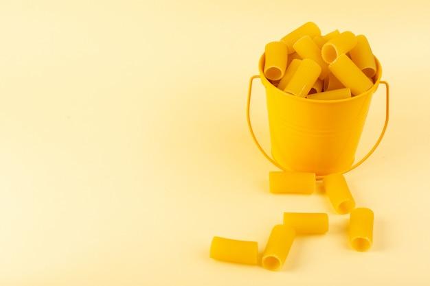バスケットの中の正面図パスタは、クリーム色の背景に黄色のバスケットの内側に生を形成しました。食事食品イタリアンスパゲッティ