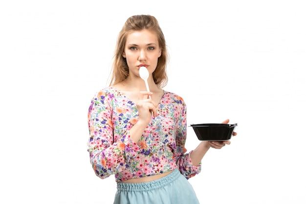 カラフルなデザインのシャツと白の黒いボウルを保持している青いスカートの正面の若い魅力的な女性