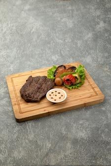 Кусочек жареного мяса с жареными овощами