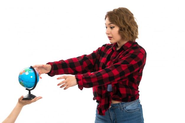 Вид спереди молодая красивая девушка в красно-черной клетчатой рубашке и синих джинсах берет маленький глобус на белом