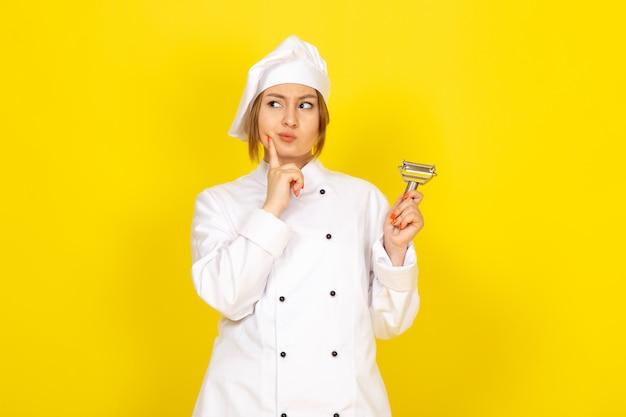 白いコックスーツと黄色の思考をポーズ野菜クリーナーを保持している白い帽子で正面の若い女性クック