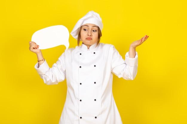 Вид спереди молодая женщина-повар в белом поварском костюме и белой кепке, держащая белый знак, не представляет позу на желтом