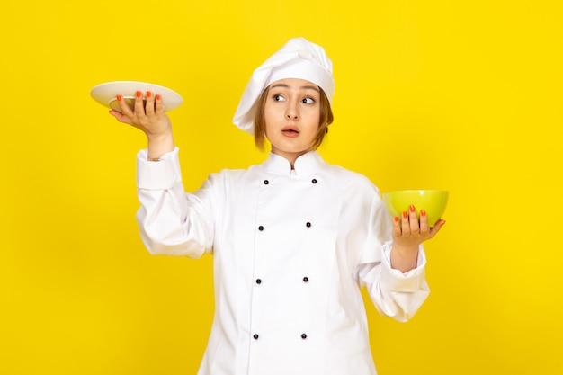 白いコックスーツと黄色の夢を見て黄色と赤のプレートを保持している白い帽子の若い女性クックの正面図