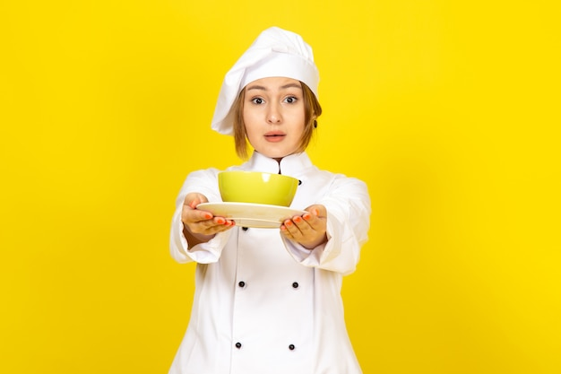 白いコックスーツと黄色に驚いた黄色と赤のプレートを保持している白い帽子の正面の若い女性クック