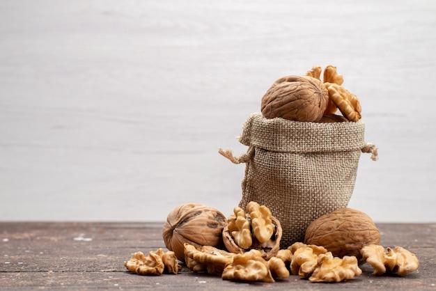 Вид спереди свежих цельных грецких орехов в скорлупе и очищенных от серой ореховой закуски.