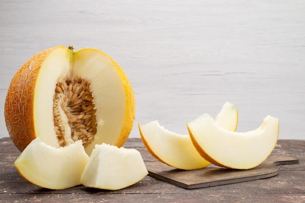正面のまろやかなメロンをスライスし、グレーのフルーツ全体を甘い果物の新鮮な甘い夏