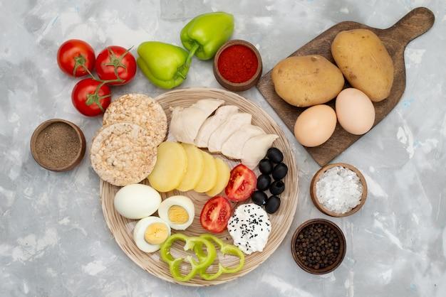 Вид сверху вареные яйца с маслинами грудки, свежие овощи и помидоры на серый, растительное питание еды завтрак