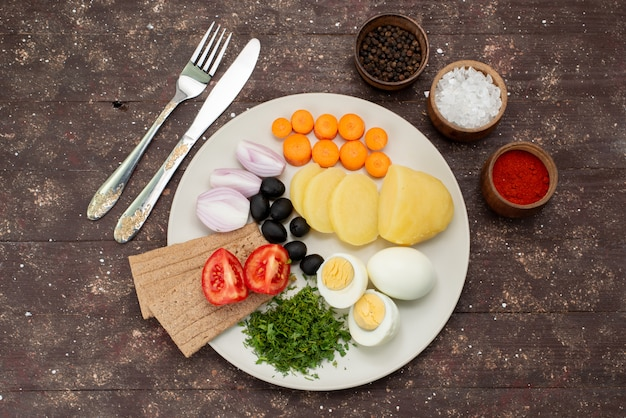 Вид сверху вареные яйца с оливками, зеленью, чесноком, приправами и помидорами на коричневой, овощной еде, завтрак