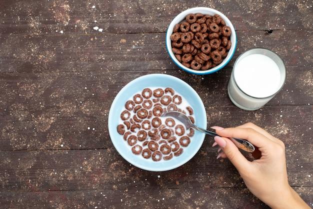 Вид сверху шоколадные хлопья с молоком внутри синюю тарелку и вместе с ложкой на коричневом