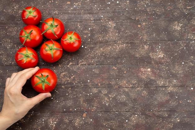 Вид сверху женщина держит помидоры спелые и свежие овощи на коричневом