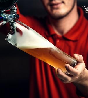 バーテンダーがグラスにビールを注ぐ