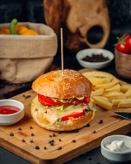 Бургер с помидорами, листьями салата, плавленым сыром и картофелем фри, кетчупом, крупным планом