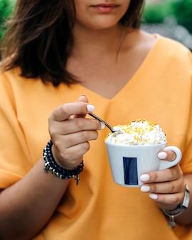 カップでデザートを食べる少女