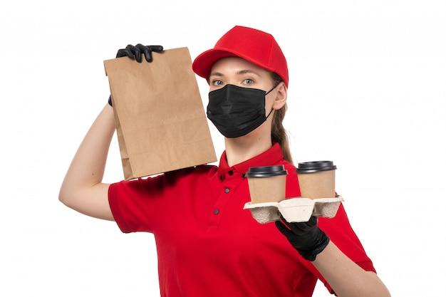 Женщина-курьер, вид спереди в красной рубашке, красной кепке, черных перчатках и черной маске с пакетами кофе и еды