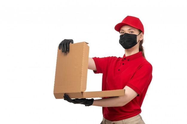 Вид спереди курьер женского пола в красной рубашке, красной шапочке, черных перчатках и черной маске с пустой коробкой для пиццы